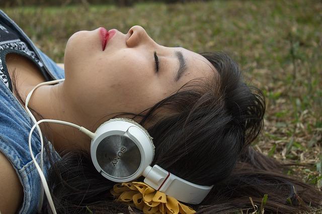 ležící dívka se sluchátky na hudbu